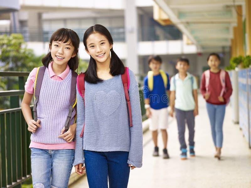 Asiatiska grundskolaflickor som går i hallet royaltyfri foto