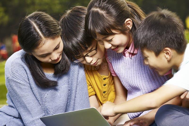 Asiatiska grundskolastudenter som tillsammans använder bärbara datorn royaltyfri foto