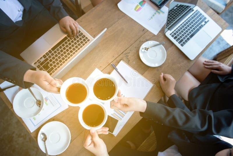 Asiatiska händer för affärskvinna som hurrar och rostar koppen kaffe med övresiktspunkt - socialt annalkande begrepp med gruppen  arkivbilder