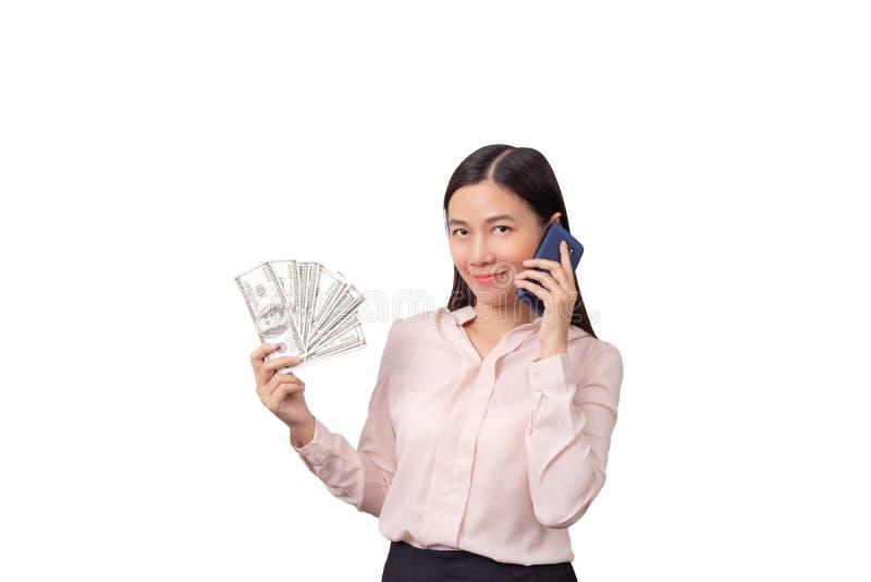 Asiatiska härliga pengar för kvinnainnehavsedel i hand och mobiltelefon i en annan hand som isoleras på vit bakgrund, urklippbana royaltyfria foton