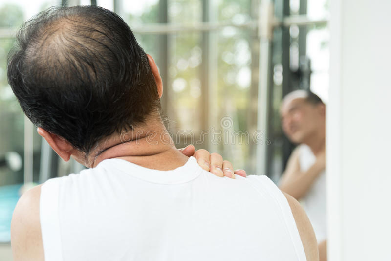 Asiatiska höga mannen som den har, smärtar på hans skuldra och hånglar arkivbild