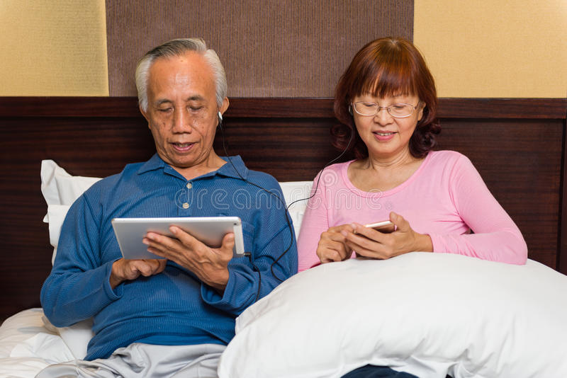 Asiatiska höga par med mobil teknologi arkivbilder