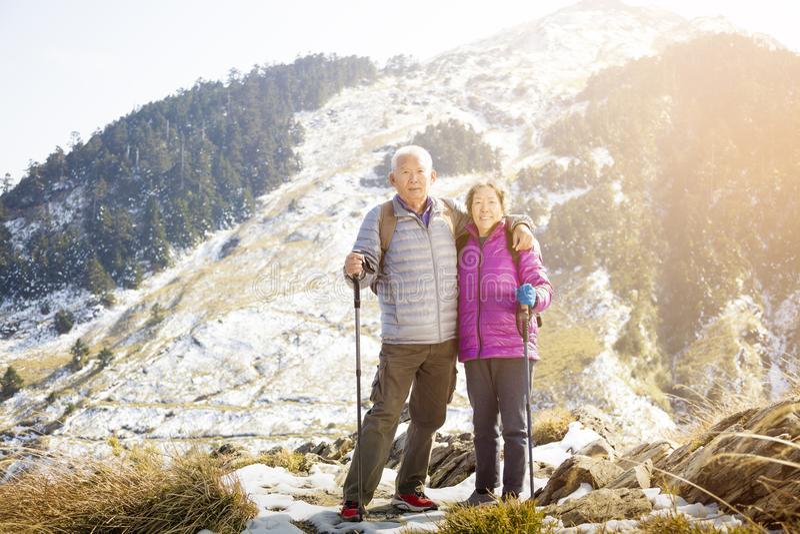 Asiatiska höga par som fotvandrar på berget royaltyfri foto
