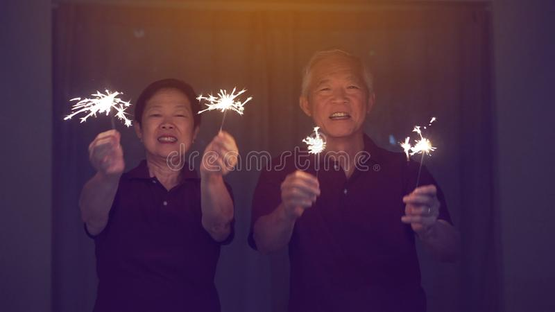 Asiatiska höga par som spelar tomtebloss, brandsmällare på natten Begrepp som firar liv royaltyfri bild
