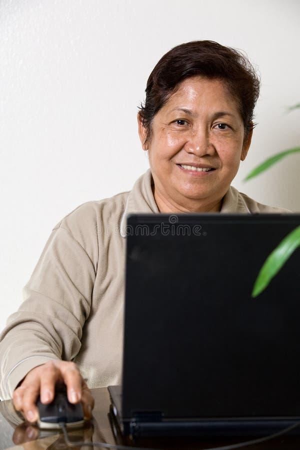 asiatiska höga sixties som ler kvinnan royaltyfri bild