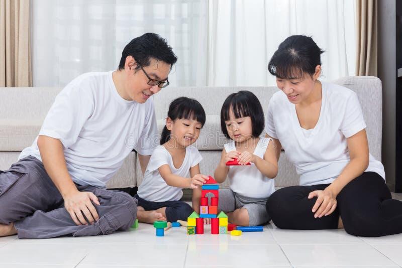 Asiatiska kinesföräldrar och döttrar som spelar kvarter på golvet arkivbild
