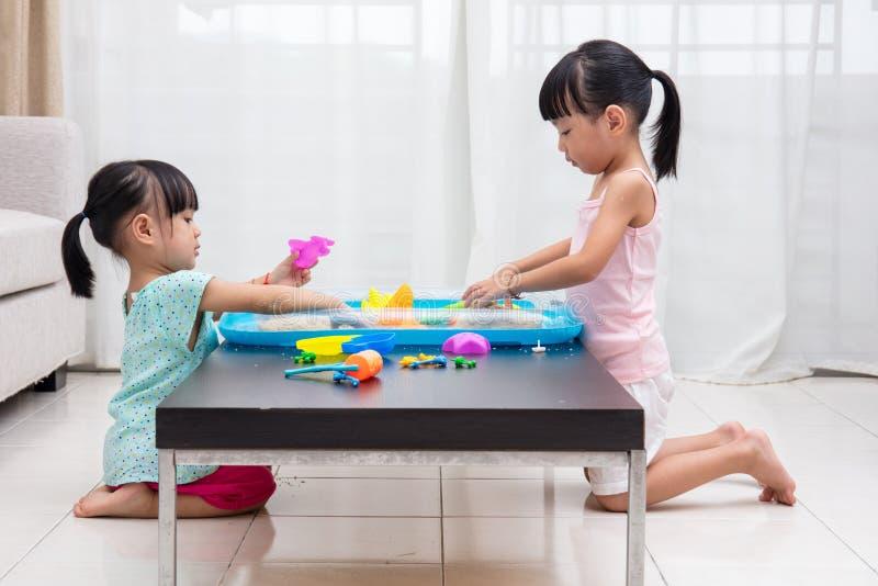 Asiatiska kinesiska små flickor som hemma spelar kinetisk sand royaltyfria bilder