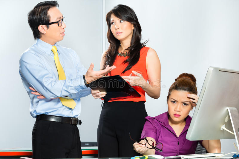 Asiatiska kollegor som mobbar eller trakasserar anställd arkivbilder