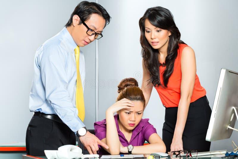 Asiatiska kollegor som mobbar eller trakasserar anställd royaltyfri foto