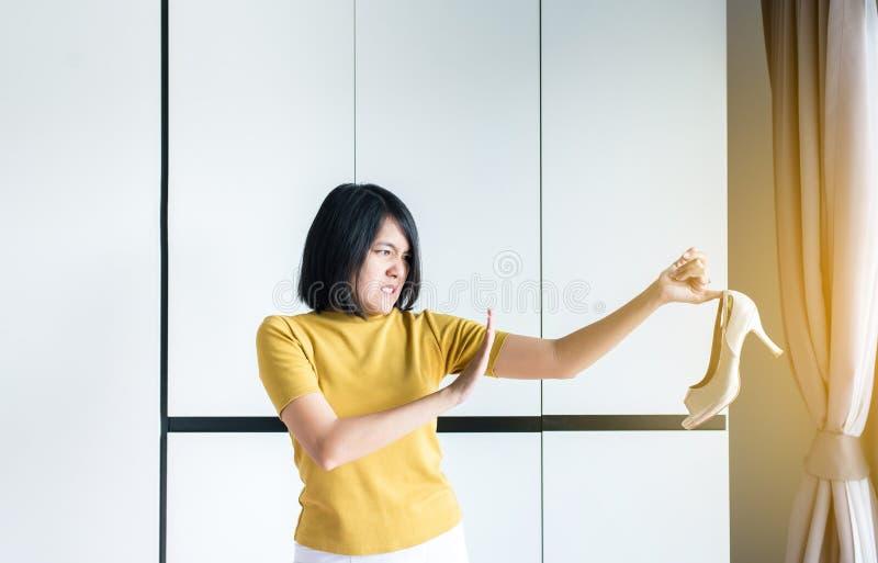 Asiatiska kvinnahänder som rymmer skon med problemet av fotlukten och den dåliga lukten som är otrevligt släcker stank royaltyfri bild