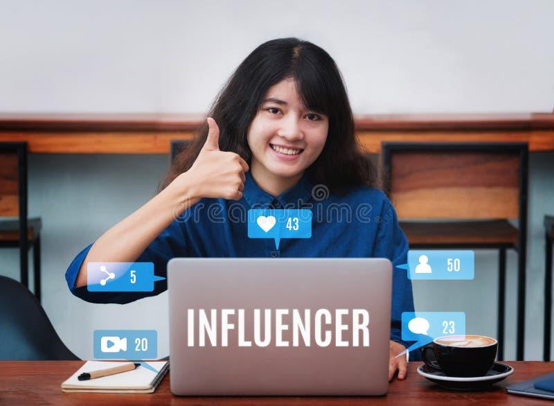 Asiatiska kvinnainfluencertummar upp och leende genom att använda bärbara datorn med cof royaltyfri fotografi