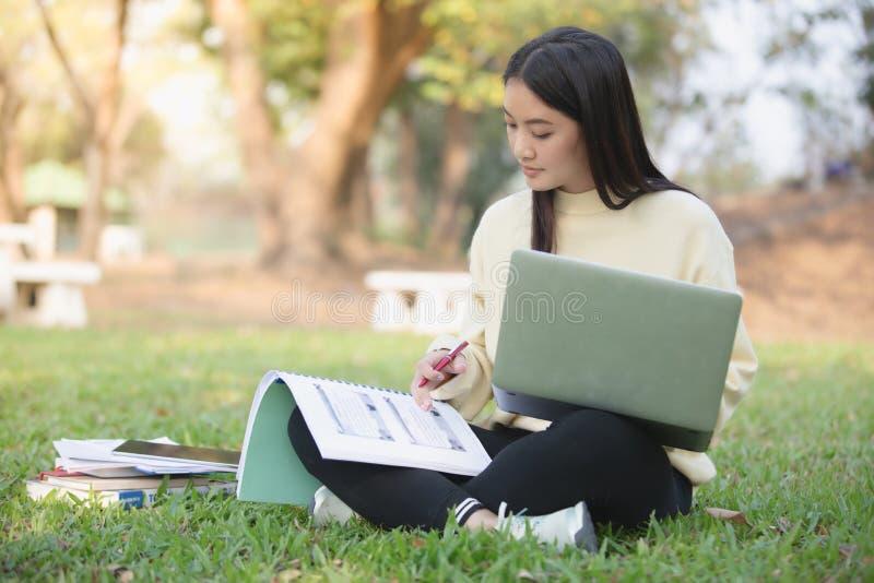 Asiatiska kvinnauniversitetsstudenter som ler och sitter på green royaltyfria bilder