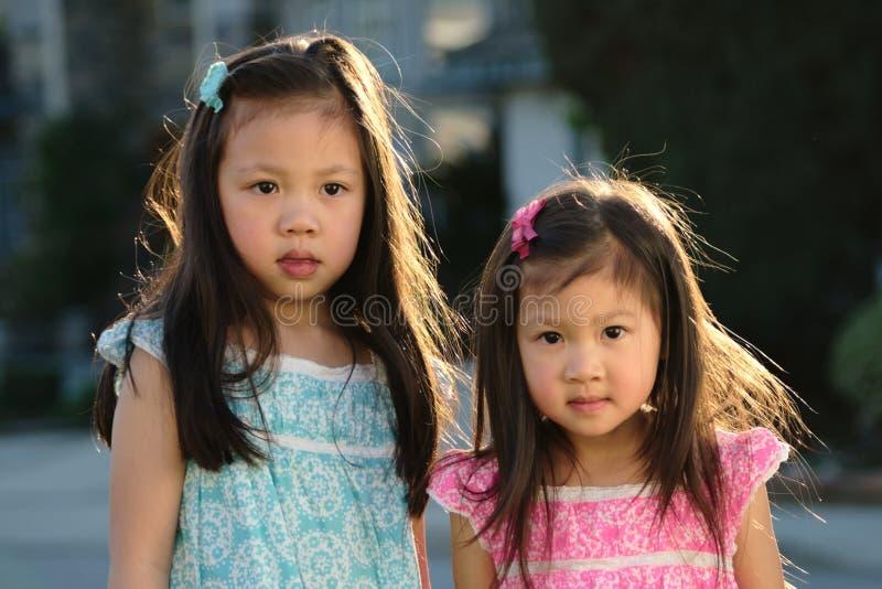 Asiatiska kvinnliga små barn som ler på kameran på solnedgången fotografering för bildbyråer