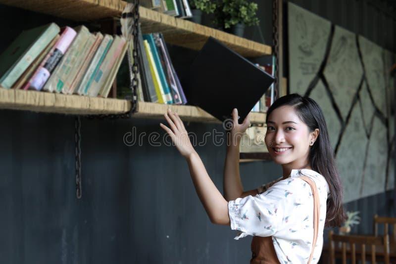 Asiatiska kvinnliga studenter som rymmer för avsnitt på bokhylla royaltyfria bilder