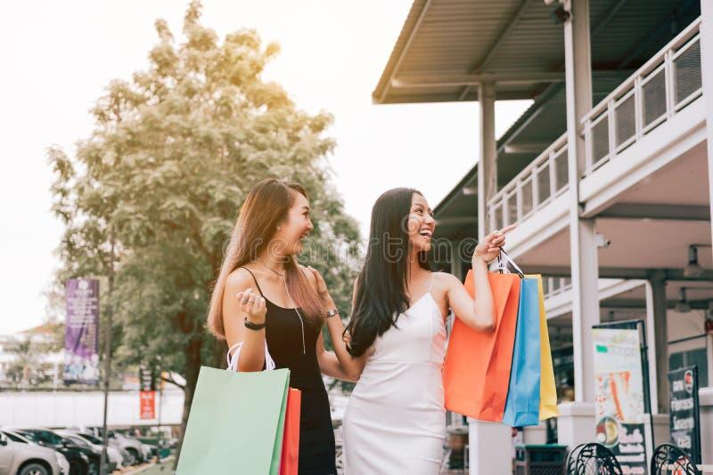 Asiatiska kvinnliga vänner som rymmer shoppingpåsen och går utanför th arkivfoton