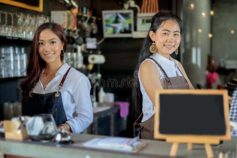 Asiatiska kvinnor Barista som ler och använder kaffemaskinen i kaffe s arkivfoto