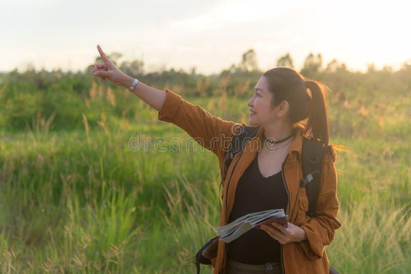 Asiatiska kvinnor för fotvandrare som går i nationalpark med ryggsäcken Gående campa för kvinnaturist i ängskogen, solnedgångsvar royaltyfria foton