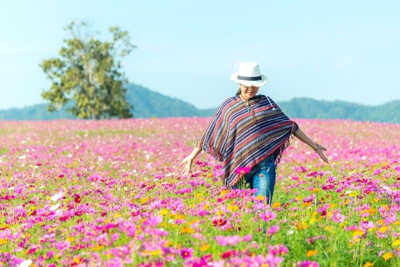 Asiatiska kvinnor för handelsresande som går i blomman för kosmos för handlag för blommafält och hand, frihet och att koppla av i arkivfoto