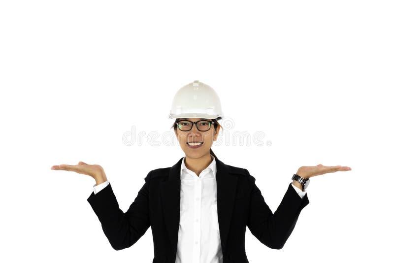 Asiatiska kvinnor för konstruktion som bär hardhaten som lyfter hennes hand som isoleras upp arkivbild