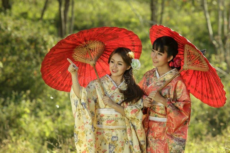 Asiatiska kvinnor för par som bär den traditionella japanska kimonot royaltyfri fotografi