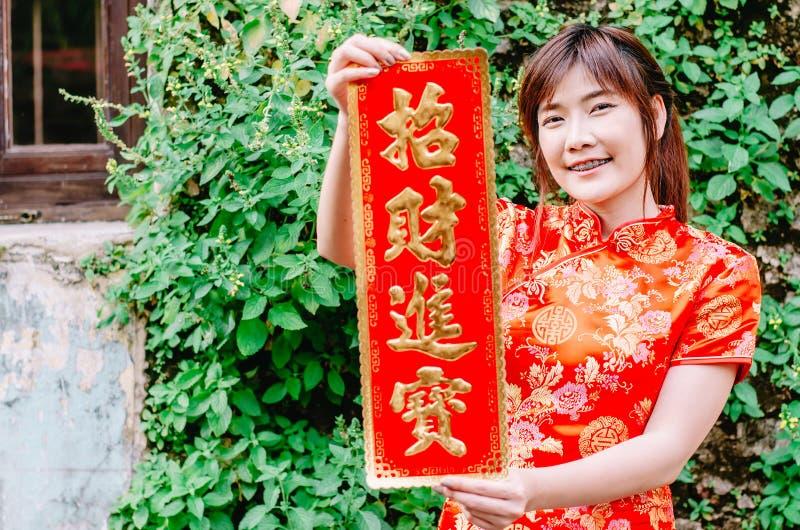 Asiatiska kvinnor i festliga dräkter som visar röda rimmat verspar med kines royaltyfri bild