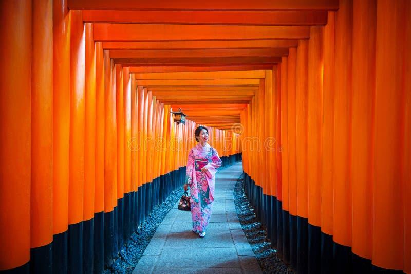 Asiatiska kvinnor i traditionella japanska kimonon på Fushimi Inari förvarar i Kyoto, Japan arkivbilder