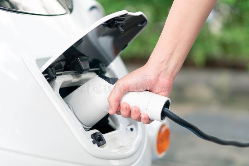 Asiatiska kvinnor kommer med batteriuppladdare förbinder med elbilen till royaltyfria bilder