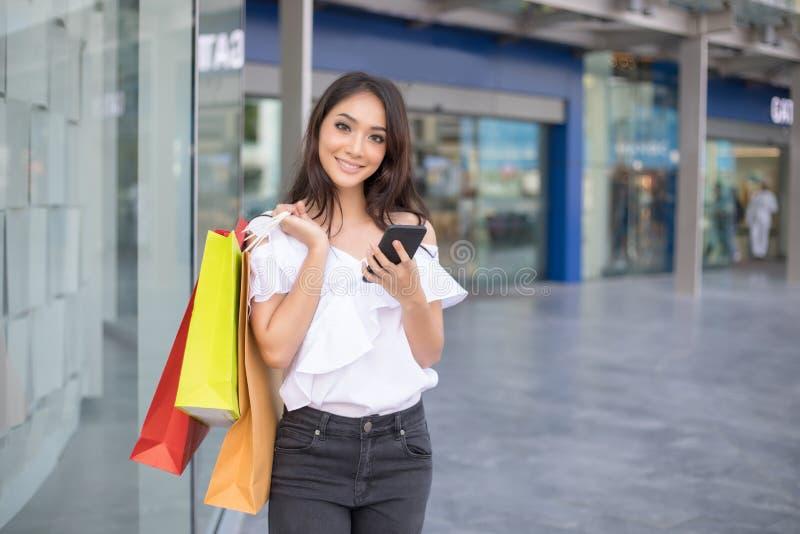 Asiatiska kvinnor och den härliga flickan är hållande shoppingpåsar och usinen royaltyfri fotografi