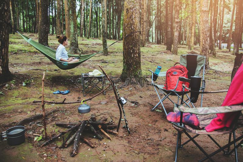 Asiatiska kvinnor reser naturligt kopplar av Sittande arbete genom att anv?nda en anteckningsbok i h?ngmattan campingplats p? den royaltyfri fotografi