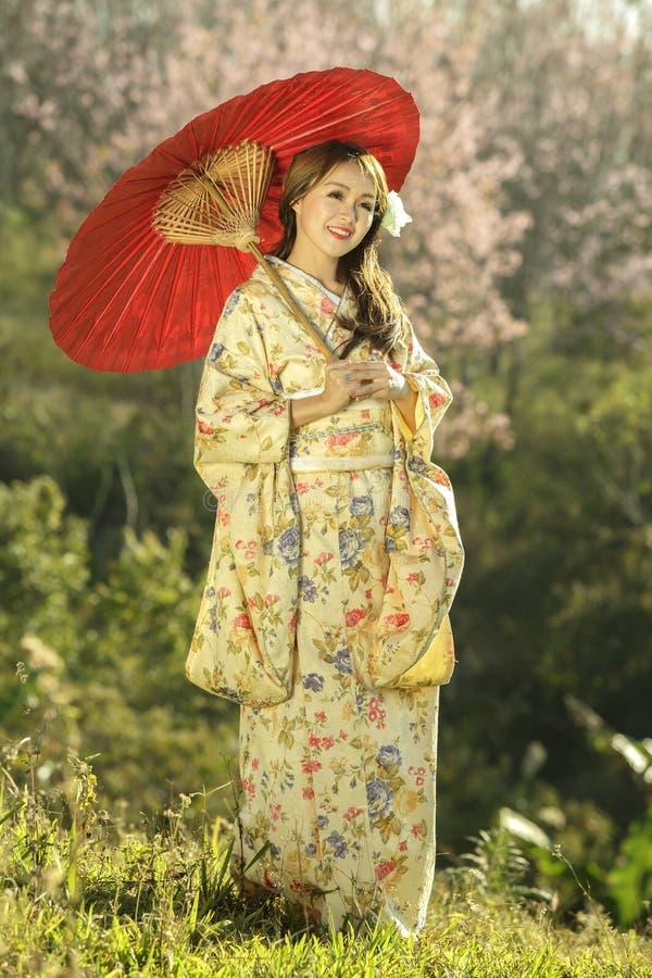 Asiatiska kvinnor som bär den traditionella japanska kimonot och det röda paraplyet royaltyfria foton