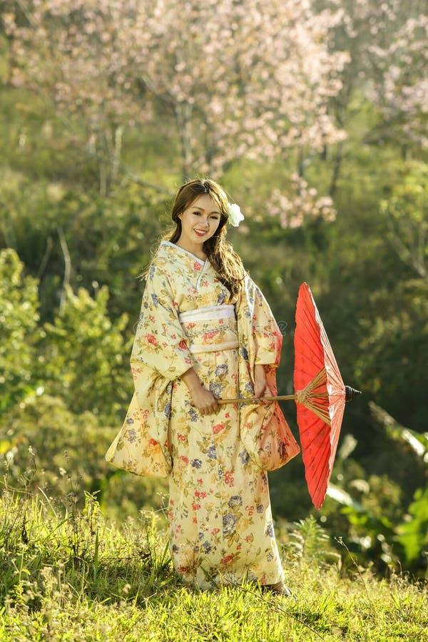 Asiatiska kvinnor som bär den traditionella japanska kimonot och det röda paraplyet arkivfoton
