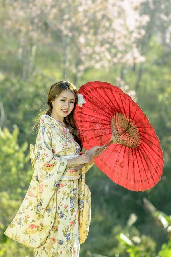 Asiatiska kvinnor som bär den traditionella japanska kimonot och det röda paraplyet arkivbild