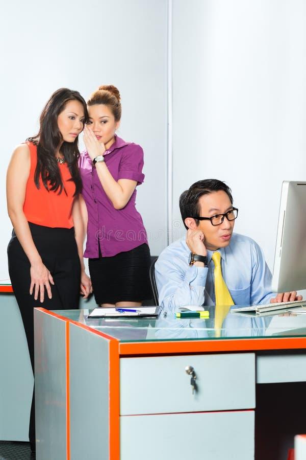 Asiatiska kvinnor som i regeringsställning trakasserar kollegan royaltyfri foto