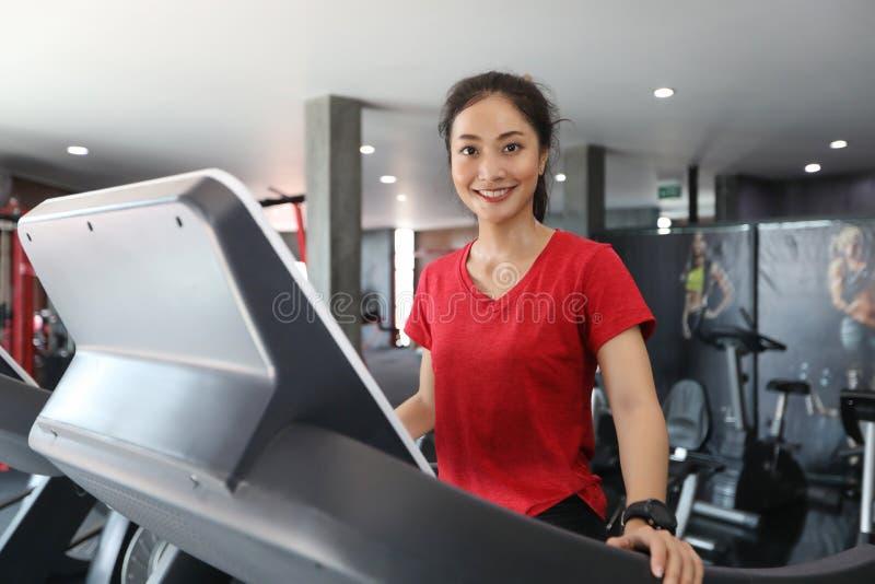 Asiatiska kvinnor som kör sportskor på idrottshallen medan en ung caucasi arkivbild