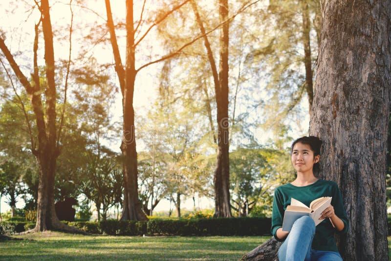 Asiatiska kvinnor som läser en bok i natur royaltyfri bild