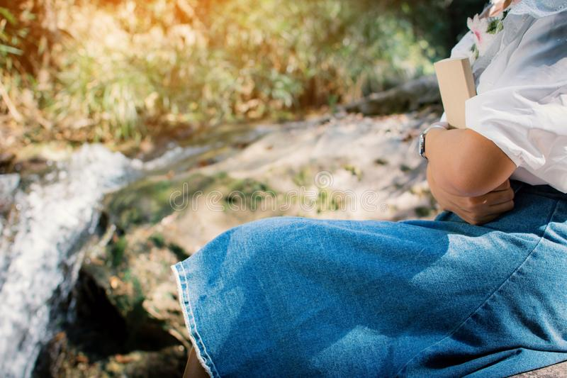 Asiatiska kvinnor som läser ett boksammanträde på vagga nära vattenfallet i skogbakgrund royaltyfria bilder