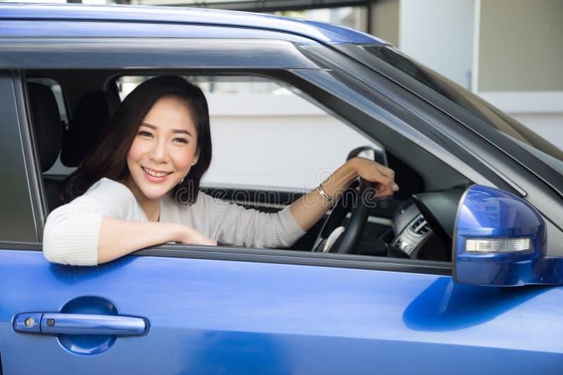 Asiatiska kvinnor som lyckligt kör en bil och ett leende med glat positivt uttryck under drevet för att resa resan, arkivfoton