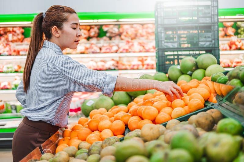 Asiatiska kvinnor som shoppar sunda matgrönsaker och frukter i supermarket royaltyfria foton