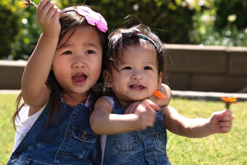 Asiatiska litet barnsystrar som utanför spelar och kramar royaltyfria bilder