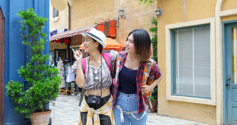 Asiatiska lyckliga kvinnaryggs?ckar som tillsammans g?r och, tar fotoet, och se bilden, koppla av tid p? feriebegreppslopp royaltyfri bild