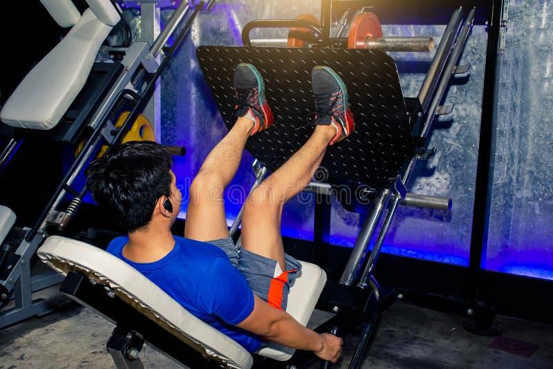 Asiatiska män övar livsstil för benpressmaskin av mannen för fitnes royaltyfria bilder