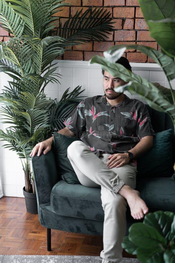 Asiatiska män bär den tropiska skjortan med svarta skägg- och brudgumblickar som sitter på soffan i konstgjord växtplats med grov royaltyfria bilder