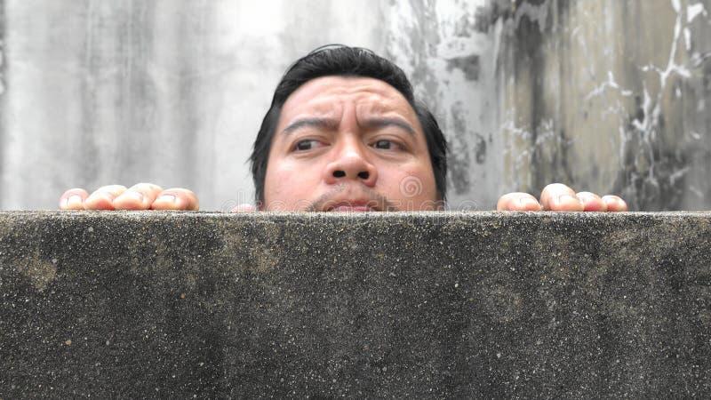 Asiatiska män klättrar upp betongväggar arkivbilder