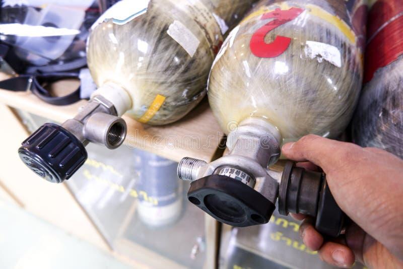 Asiatiska män kontrollerar syrebehållare fotografering för bildbyråer