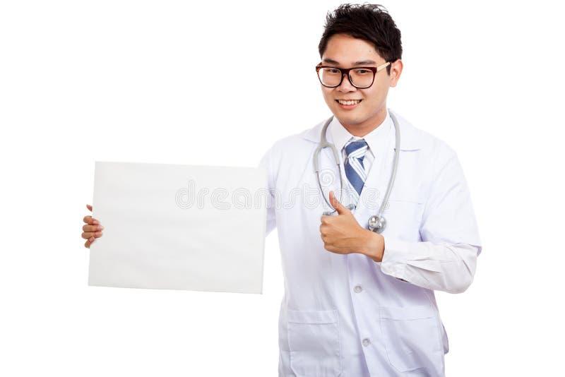 Asiatiska manliga doktorstummar upp med det tomma tecknet arkivfoton