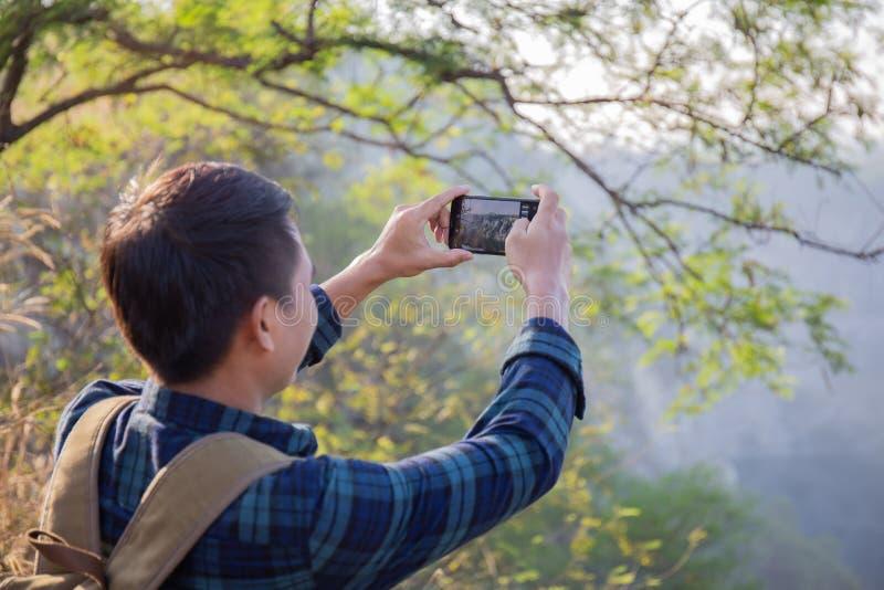 Asiatiska manliga handelsresande anv?nder en smartphone f?r att ta bilder av h?rligt landskap royaltyfri bild