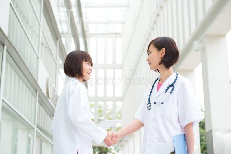 Asiatiska medicinska doktorer som skakar händer fotografering för bildbyråer