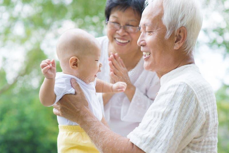 Asiatiska morföräldrar som spelar med sonsonen fotografering för bildbyråer