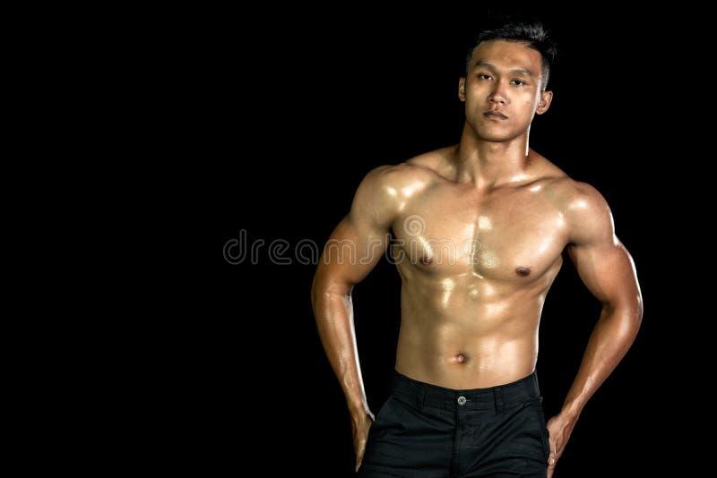 Asiatiska muskelmän med muskelfront mot svart bakgrund Kroppsgym, bröstkorg och bog samt buk Hälsosam kroppstyp fotografering för bildbyråer