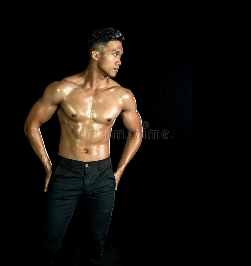 Asiatiska muskelmän med muskelfront mot svart bakgrund Kroppsgym, bröstkorg och bog samt buk Hälsosam kroppstyp royaltyfria foton
